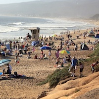 Crowds of people enjoying the sun and beach in Half Moon Bay